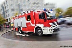 Ein Feuerwehrwagen fährt mit hoher Geschwindigkeit. Das Bild ist aufgrund der dargestellten Geschwindigkeit verwischt.